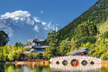 chinese culture: Amazing view of the Jade Dragon Snow Mountain and the Suocui Bridge over the Black Dragon Pool in the Jade Spring Park, Lijiang, Yunnan province, China.