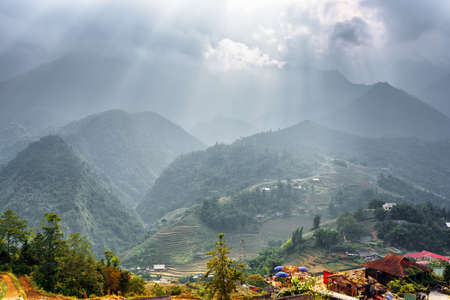 lien: Scenic view of rays of sunlight through stormy clouds at highlands of Sapa District, Lao Cai Province, Vietnam. The Hoang Lien Mountains and rice terraces are visible in background. Stock Photo