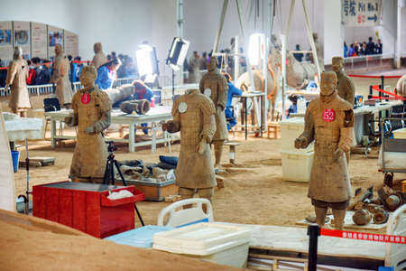 archaeologist: XIAN, SHAANXI PROVINCE, CHINA - OCTOBER 28, 2015: Chinese archaeologists working at excavation site of the famous Terracotta Army in the Qin Shi Huang Mausoleum of the First Emperor of China. Editorial