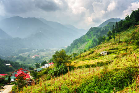 lien: Scenic view of houses of Cat Cat Village and the Hoang Lien Mountains at Sapa, Lao Cai Province, Vietnam. Stormy dramatic cloudy sky in background. Sa Pa is a popular tourist destination of Asia.