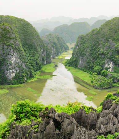 ngo: Top view of the Ngo Dong River at the Tam Coc portion, Ninh Binh Province, Vietnam. Landscape formed by karst towers and rice fields. Scenic mountains are visible in background.