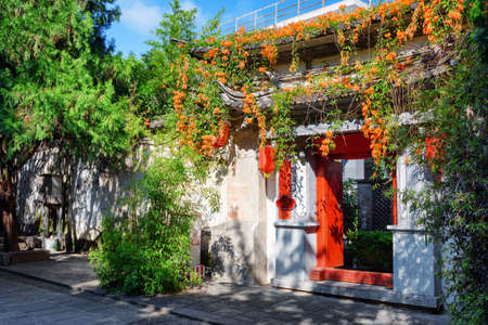 old town house: Red doors leading into courtyard of traditional Chinese house in Dali Old Town, Yunnan province, China. Gate decorated with flowers. Ancient city of Dali is a popular tourist destination of Asia.