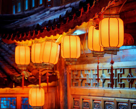 china: Night view of row of traditional Chinese red street lanterns on carved facade of wooden house in the Old Town of Lijiang, Yunnan province, China. Focus on the first lantern. Stock Photo