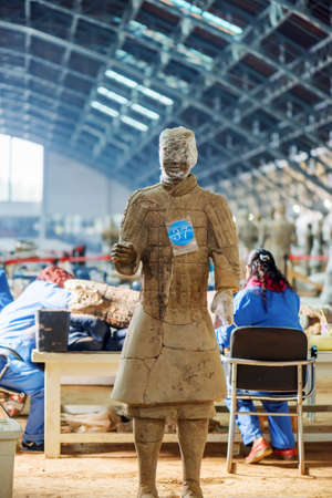 archaeologists: XIAN, SHAANXI PROVINCE, CHINA - OCTOBER 28, 2015: Chinese archaeologists working at excavation site of the Terracotta Army in the Qin Shi Huang Mausoleum of the First Emperor of China.