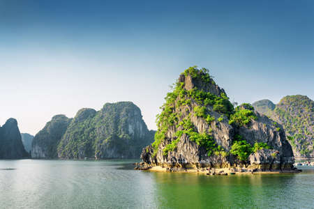 halong: Beautiful view of the Halong Bay (Descending Dragon Bay) at the Gulf of Tonkin of the South China Sea, Vietnam. Landscape formed by karst towers-isles in various sizes. Blue sky in background. Stock Photo