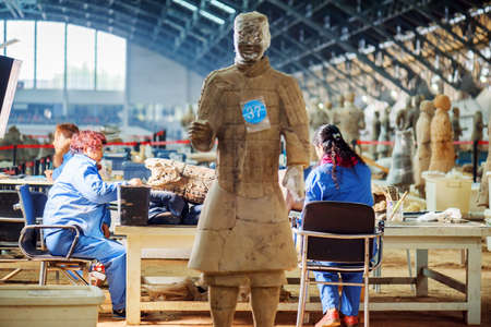 emperor of china: XIAN, SHAANXI PROVINCE, CHINA - OCTOBER 28, 2015: Chinese archaeologists working at excavation of the famous Terracotta Army inside the Qin Shi Huang Mausoleum of the First Emperor of China.