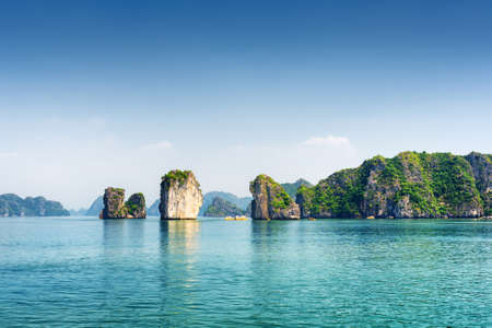 Azure water of the Ha Long Bay at the Gulf of Tonkin of the South China Sea, Vietnam. Scenic view of blue lagoon and karst towers-isles. The Halong Bay is a popular tourist destination of Asia. Banque d'images
