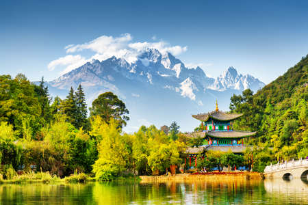 Scenic view of the Jade Dragon Snow Mountain and the Moon Embracing Pavilion on the Black Dragon Pool in the Jade Spring Park, Lijiang, Yunnan province, China.