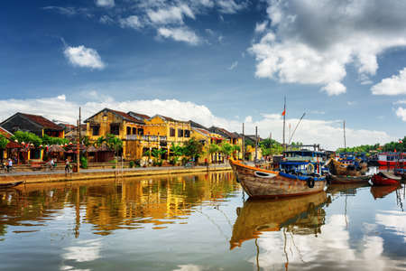 towns: Wooden boats on the Thu Bon River in Hoi An Ancient Town (Hoian), Vietnam. Scenic yellow old houses on waterfront reflected in river. Hoi An is a popular tourist destination of Asia. Stock Photo