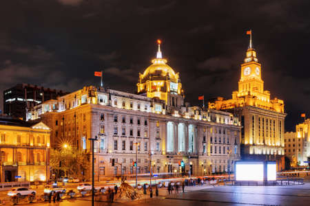 tower house: Night view of the Bund (Waitan), Shanghai, China. The Shanghai Custom House building with clock tower is visible at right, the HSBC Building (the Municipal Government Building) at left.