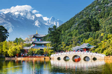 Beautiful view of the Jade Dragon Snow Mountain and the Suocui Bridge over the Black Dragon Pool in the Jade Spring Park, Lijiang, Yunnan province, China.