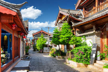 destination scenic: Scenic view of narrow street in the Old Town of Lijiang, Yunnan province, China. The Old Town of Lijiang is a popular tourist destination of Asia.
