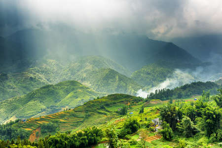 lien: Amazing view of rice terraces at highlands and rays of sunlight through storm clouds in the Hoang Lien Mountains of Sapa District, Lao Cai Province, Vietnam. Sa Pa is a popular tourist destination. Stock Photo