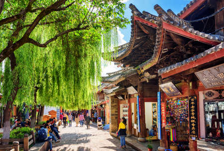 destination scenic: LIJIANG, YUNNAN PROVINCE, CHINA - OCTOBER 23, 2015: Souvenir shops on scenic street of the Old Town of Lijiang. The Old Town of Lijiang is a popular tourist destination of Asia.