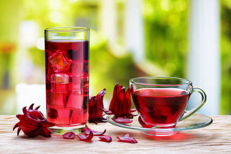 sepals: Cup of hot hibiscus tea (karkade, red sorrel, Agua de flor de Jamaica) and the same cold drink with ice cubes in glass on wooden table. Drink made from magenta calyces (sepals) of roselle flowers. Stock Photo