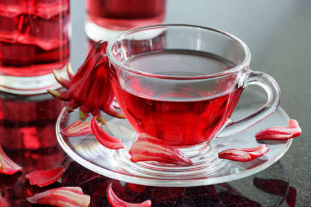 flor: Cup of hibiscus tea (rosella, karkade, red sorrel, Agua de flor de Jamaica) on table. Drink made from magenta calyces (sepals) of roselle flowers. Healthy herbal tea rich in vitamin C and minerals.