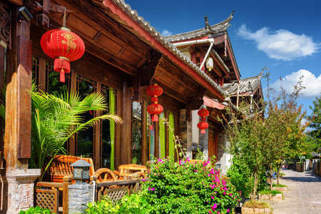 Wooden facade of traditional Chinese house decorated with red lanterns in the Old Town of Lijiang, Yunnan province, China. The Old Town of Lijiang is a popular tourist destination of Asia.