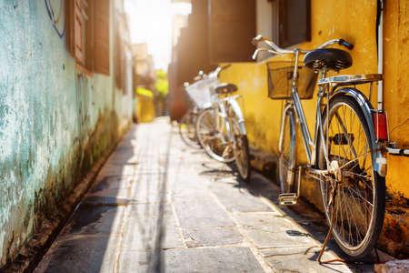 bicicleta: Bicicletas aparcadas cerca de la pared amarilla de la casa vieja en la calle soleada en verano. Hoi una ciudad antigua (Hoian), Vietnam. Hoi An es un popular destino tur�stico de Asia. Foto de archivo