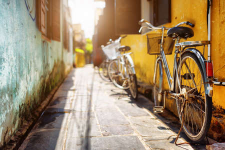 Bicycles parked near yellow wall of old house on sunny street in summer. Hoi An Ancient Town (Hoian), Vietnam. Hoi An Ancient Town is a popular tourist destination of Asia.