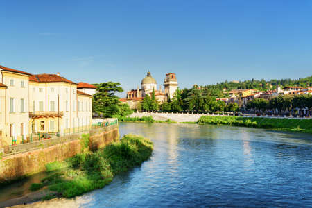 destinations: View of the Adige River and the Church of San Giorgio in Braida, Verona, Italy. Blue sky in background. Verona is a popular tourist destination of Europe. Stock Photo