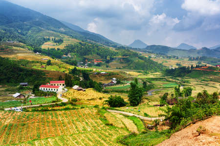 lao: View of village and terraced rice fields at highlands of Sapa District, Lao Cai Province, Vietnam. Sa Pa is a popular tourist destination of Asia. Dramatic sky in background. Stock Photo