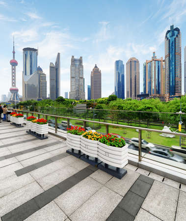 century: Modern view of skyscrapers and park in the Pudong New District (Lujiazui) of Shanghai, China. The Oriental Pearl Tower is visible at left. View from pedestrian side of Century Avenue.