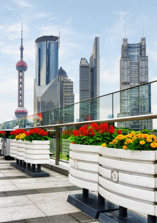 huangpu: Modern view of skyscrapers in city business center of the Pudong New District (Lujiazui), Shanghai, China. The Oriental Pearl Tower in downtown is visible at left. Outdoor flower pots.