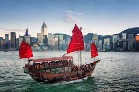Tourists on traditional Chinese wooden sailing ship crosses Victoria harbor. Scenic view of the Hong Kong Island skyline at evening. Skyscrapers in downtown are visible from Kowloon side.