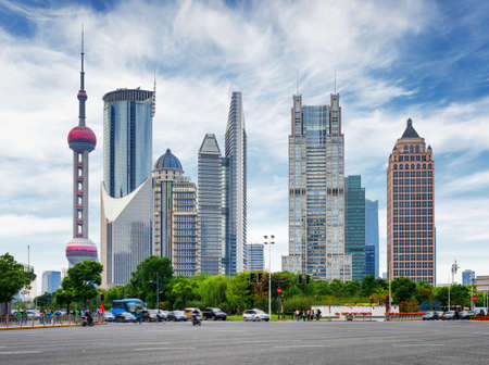 pudong district: View of intersection of Century Avenue and Lujiazui Ring Road in the Pudong New District of Shanghai, China. Skyscrapers of downtown on blue sky background. The Oriental Pearl Tower is visible at left