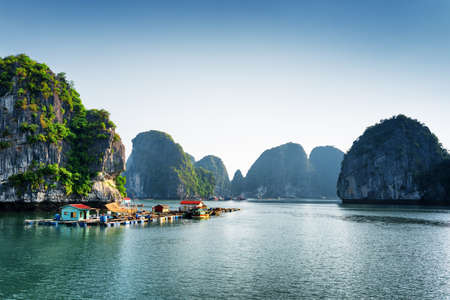 Scenic view of floating fishing village in the Halong Bay (Descending Dragon Bay) at the Gulf of Tonkin of the South China Sea, Vietnam. Landscape formed by karst towers-isles in various sizes.