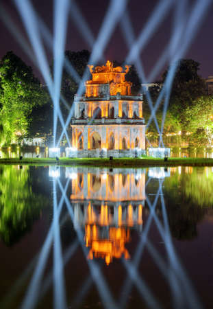 returned: Night view of the Turtle Tower among blue light rays in middle of the Hoan Kiem Lake (Lake of the Returned Sword) at historic centre of Hanoi, Vietnam. The tower reflected in the lake.