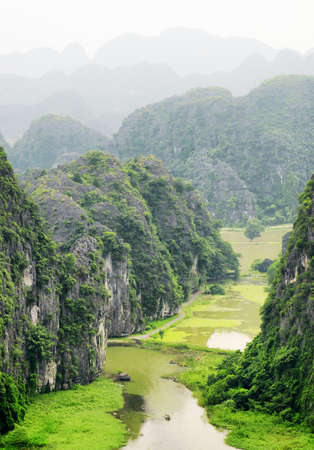 ngo: Top view of the Ngo Dong River and rice fields at the Tam Coc portion, Ninh Binh Province, Vietnam. Landscape formed by karst towers. Scenic mountains are visible in background. Stock Photo