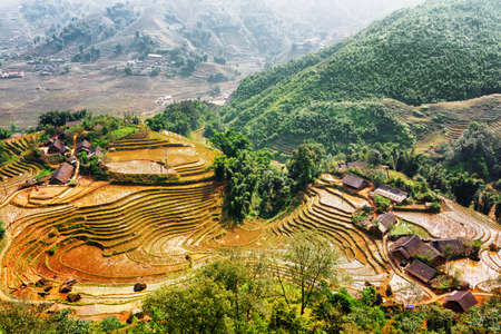 lien: Top view of village houses and rice terraces filled with water in the Hoang Lien Mountains in autumn. Sapa District, Lao Cai Province, Vietnam. Sa Pa is a popular tourist destination of Asia.