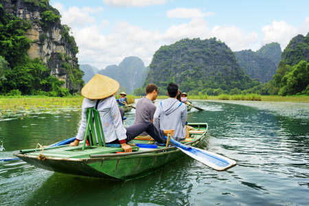 Tourists traveling in boat along the Ngo Dong River at the Tam Coc portion, Ninh Binh Province, Vietnam. Rower using her feet to propel oars. Scenic landscape formed by karst towers and rice fields. Stock Photo