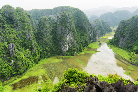 ngo: Top view of karst towers, rice fields and the Ngo Dong River at the Tam Coc, Ninh Binh Province, Vietnam. Scenic mountains are visible in background. The Tam Coc is a popular tourist destination.