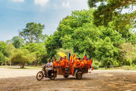 motorised: Siem Reap, Camboya - 2 de mayo, 2015: monjes budistas en vehículo motorizado que viajan al antiguo complejo de templos de Angkor Wat Siem Reap, Camboya. Bosques y cielo azul en el fondo.