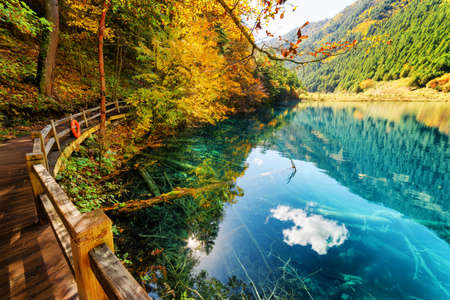 Wooden boardwalk leading along amazing lake with azure crystal clear water among fall woods and mountains. Autumn forest and sky reflected in water. Submerged tree trunks are visible on the bottom. Stockfoto