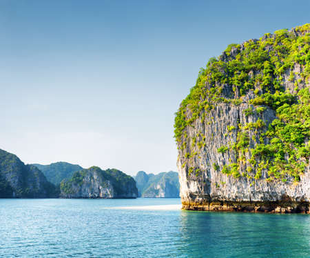 destination scenic: Scenic karst tower-isle in the Ha Long Bay (Descending Dragon Bay) at the Gulf of Tonkin of the South China Sea, Vietnam. The Halong Bay is a popular tourist destination of Asia.