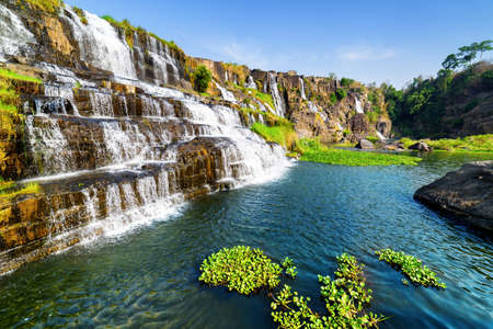 destination scenic: Beautiful view of natural cascading waterfall with crystal clear water and scenic pool among rocks in summer. Sunny landscape in Vietnam. The Pongour waterfall is a popular tourist destination of Asia Stock Photo