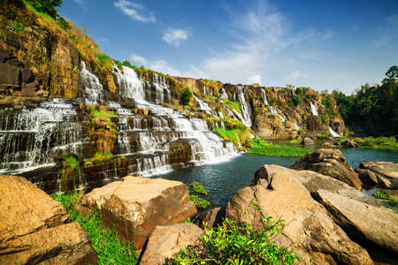 the natural world: Amazing view of natural cascading waterfall with crystal clear water, Vietnam. Summer sunny landscape. Blue sky in background. The Pongour waterfall (PonGour) is a popular tourist destination of Asia. Stock Photo