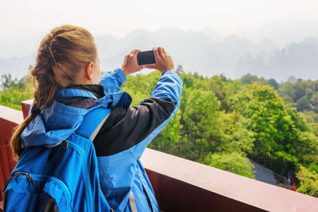 plait: Closeup view of young female tourist with smartphone taking photo and enjoying mountain view in the Zhangjiajie National Forest Park, Hunan Province, China. Her hair braided in French plait.