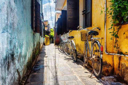 Le biciclette hanno parcheggiato vicino alla parete gialla di vecchia casa sulla via stretta nella città antica di Hoi An (Hoian), Vietnam. Hoi An Ancient Town è una popolare destinazione turistica dell'Asia.