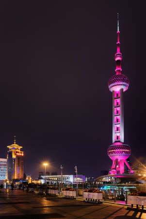 century: Night view of the Oriental Pearl Tower from pedestrian side of Century Avenue in downtown, the Pudong New District (Lujiazui) of Shanghai, China. The famous tower glows pink.