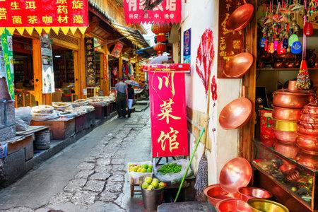 伝統: LIJIANG, YUNNAN PROVINCE, CHINA - OCTOBER 23, 2015: Traditional oriental Chinese handmade utensils and copper hot pots (steamboats) at gift shop on scenic narrow street in the Old Town of Lijiang. 報道画像