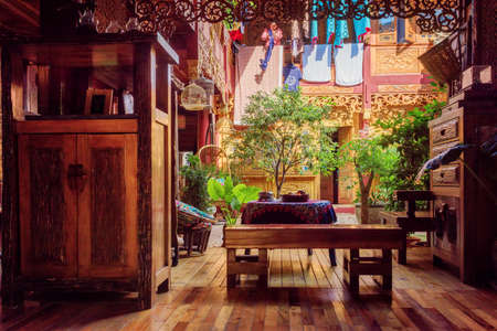 LIJIANG, YUNNAN PROVINCE, CHINA - OCTOBER 23, 2015: Beautiful cozy courtyard of traditional oriental Chinese wooden house with amazing carved walls. Courtyard decorated with potted green plants. Editorial
