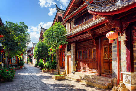 LIJIANG, YUNNAN PROVINCE, CHINA - OCTOBER 23, 2015: Scenic view of cozy street in the Old Town of Lijiang. Carved wooden facades of traditional oriental Chinese houses decorated with red lanterns.