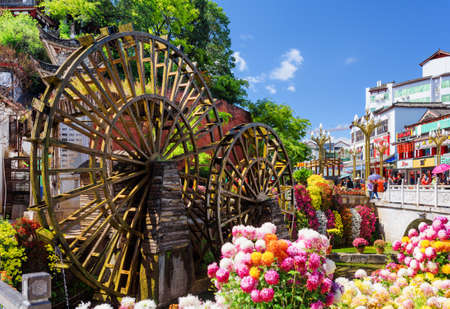 water town: LIJIANG, YUNNAN PROVINCE, CHINA - OCTOBER 23, 2015: Ornamental water mills and colorful flowers at the main entrance to the Old Town of Lijiang. Lijiang is a popular tourist destination of Asia.