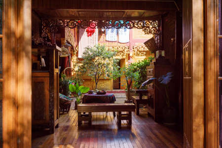 chinese courtyard: LIJIANG, YUNNAN PROVINCE, CHINA - OCTOBER 23, 2015: Amazing cozy courtyard of traditional oriental Chinese wooden house with beautiful carved walls. Courtyard decorated with potted green plants.