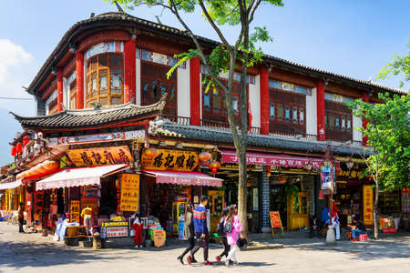 traditional house: DALI, YUNNAN PROVINCE, CHINA - OCTOBER 21, 2015: Amazing colorful wooden facade of traditional Chinese house in Dali Old Town. Scenic view of souvenir shops on street of the ancient town.