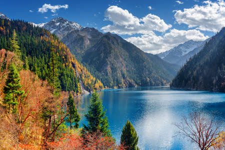 long lake: Beautiful view of the Long Lake among colorful fall woods and snow-capped mountains in Jiuzhaigou nature reserve (Jiuzhai Valley National Park), China. Amazing snowy peaks are visible in background. Stock Photo